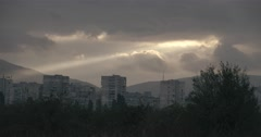 Sunbeam penetrates the dark clouds over the city Stock Footage