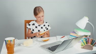 Schoolgirl making sandwich with butter sitting at the desk Stock Footage