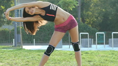 Pretty young girl doing exercise for flexibility on the street in full HD Stock Footage