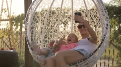 Young mom and cute daughter take selfie photo via smart phone swaying on swing Stock Footage