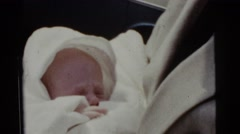 1961: father talking to sleeping baby DETROIT, MICHIGAN Stock Footage