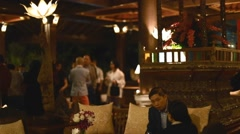 Guests chatting in the peaceful ambience of an open air restaurant Stock Footage