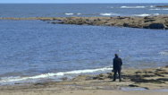 A man walks on a rocky beach. Stock Footage