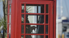 Man talking on the phone in a red telephone booth. Stock Footage