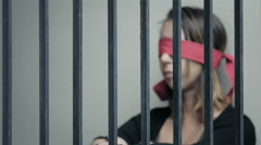 Young woman blindfolded behind prison bars Stock Footage