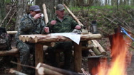 Two men in military uniform sitting at a table of logs in a transit camp in the Stock Footage