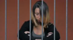 Desperate prisoner sitting behind bars Stock Footage