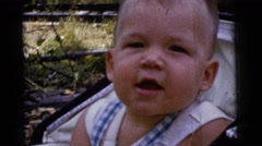 1961: babbling baby boy in vintage stroller in wooded park DETROIT, MICHIGAN Stock Footage