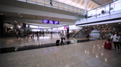 Panoramic view of interior of Hong Kong airport with many passengers all around Stock Footage