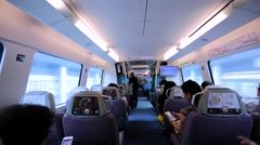 Walking between comfortable seats in Hong Kong train driving fast to the airport Stock Footage