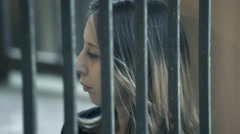 Young prisoner behind bars thinks sadly to her fate Stock Footage