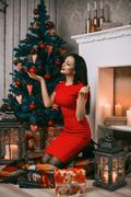 Girl decorate the Christmas tree in a house interior Stock Photos