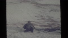1963: a man lying on the snow and skating down fast along the hill CAMDEN, NEW Stock Footage