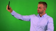 Young handsome business man photographs with smartphone (selfie) - green screen  Stock Footage