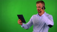 Young business man works on tablet and phone with smartphone - green screen Stock Footage