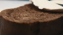Butter knife rubs butter or cottage cheese on piece of bread. Tilt shift Stock Footage