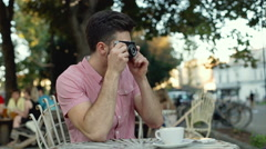 Man using old, vintage camera while sitting in the outdoor cafe Stock Footage
