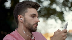 Handsome man relaxing outdoors and listening music on earphones Stock Footage