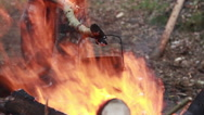 A man in military uniform to boil water in a kettle on a fire in the forest Stock Footage