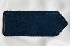 Pointer made of denim fabric with yellow stitching on white silk Stock Photos