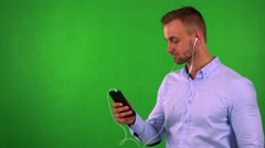 Young business man listens music with earphone on smartphone - green screen Stock Footage