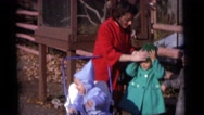 1963: women is fixing a child's hats. she is with three young infant and they Stock Footage