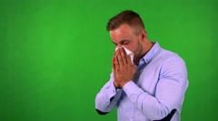 Young handsome business man blow one's nose - green screen - studio Stock Footage