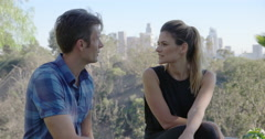 Non-smoking boyfriend is replaced by smoker with young woman in LA park 4K Stock Footage