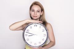 Beautiful young woman looking at a large silver retro clock that she is holding Stock Photos