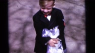 1963: a woman, two boys and a girl are dressed up, standing, and moving  Stock Footage