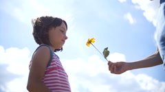 Boy Gives a Girl a Flower on a Sky Background, boy gives a girl a gift Stock Footage