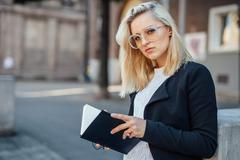 Young business woman is looking at the camera and holding notepad. City backg Stock Photos