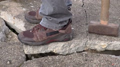 Worker with sledgehammer on broken concrete slabs Stock Footage