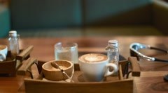 A wooden tray presents a coffee with latte art and raw sugar Stock Footage