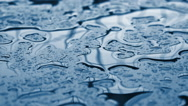 Raindrops falling in slow motion on metal surface Stock Footage