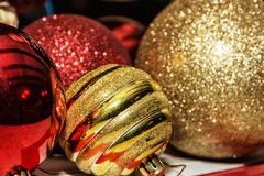 Red and yellow shimmering christmas baubles Stock Photos