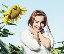 Beautiful smiling woman posing with sunflower, beauty and nature Stock Photos