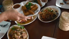 A table full of traditional thai food with sticky rice in the round baskets Stock Footage