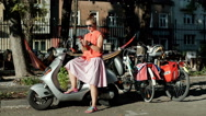 Woman sitting on her scooter and having a conversation on cellphone Stock Footage
