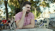 Handsome man chatting on cellphone in the outdoor cafe and smiling to the camera Stock Footage
