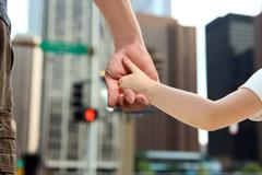 Father holding  the daughter/ child  hand  behind  the traffic lights Stock Photos