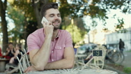 Handsome, stylish man sitting in the outdoor cafe and chatting on cellphone Stock Footage