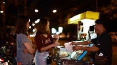 Thai girl gets her street food order and pays the vendor Stock Footage