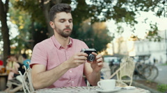 Handsome man pretends to be a photographer and smiling to the camera Stock Footage