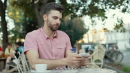 Man wins the game while playing on smartphone in the outdoor cafe Stock Footage