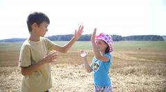 Boy with girl playing patty cake in the field, slow motion Stock Footage