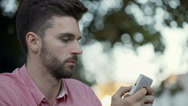 Thoughtful man sitting outdoor and texting on smartphone Stock Footage
