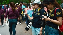 Thai girls in a crowd with professional cameras having a chat Stock Footage