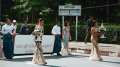 Thai people carry bouquet of flowers through the streets Stock Footage