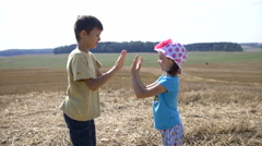 Boy with girl playing patty cake in the field Stock Footage